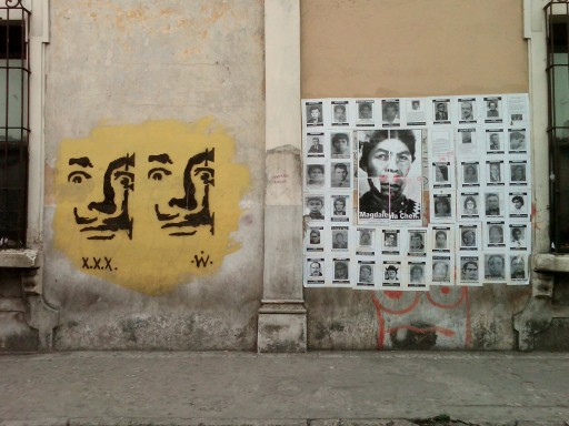 Posters showing the faces of people disappeared and killed by the Guatemalan state alongside graffiti depicting Salvador Dali, Guatemala City