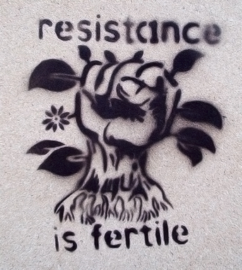 stencil graffiti showing a spray-painted fist with leaves, flowers, and roots going out of it, surrounded by the words