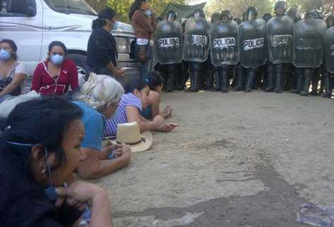 Women protesters lie down in the road in front of riot police. Photo: Guatemala Indymedia